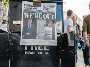 "A group of people stand alongside a newspaper announcing Great Britain's ""Brexit"" from the EU"