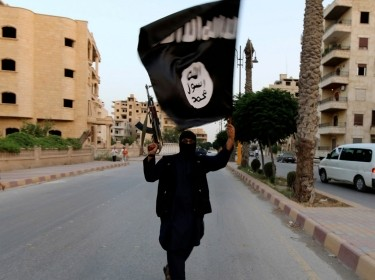 An ISIS militant waves an ISIS flag in Raqqa, Syria, June 29, 2014