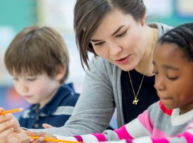 A teacher helps a student