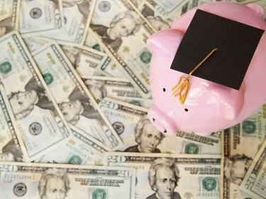 a piggy bank with a graduation cap surrounded by U.S. currency