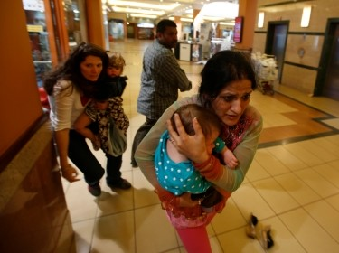 Women carrying children run for safety as armed police hunt gunmen who went on a shooting spree in Westgate shopping centre in Nairobi September 21, 2013