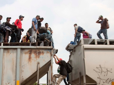 Migrants climb off a train during their journey toward the U.S.-Mexican border