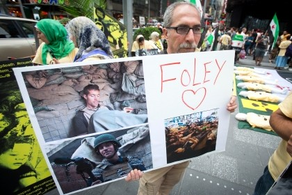 A man holds up a sign in memory of U.S. journalist James Foley during a protest against the Assad regime in Syria in New York City, Aug. 22, 2014