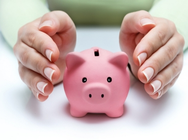 Hands held around a pink piggy bank