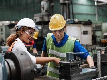 Man and woman engineer industry worker wearing hard hat in factory, photo by eakgrungenerd/AdobeStock