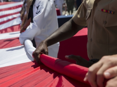 U.S. service members unfurl the United States flag during a Memorial Day ceremony at the Intrepid Sea, Air, and Space Museum as part of Fleet Week New York in New York City NY, May 27, 2019.