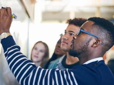 Young man writing on a whiteboard while students look on