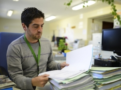 A male office worker reads files at his desk