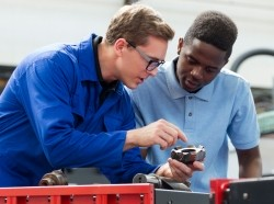 A young man learns as an apprentice in a manufacturing setting