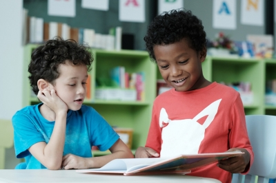 American and African boys are reading and studying together with happiness in their classroom, kid education concept, photo