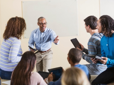 A teacher interacts enthusiastically with his students