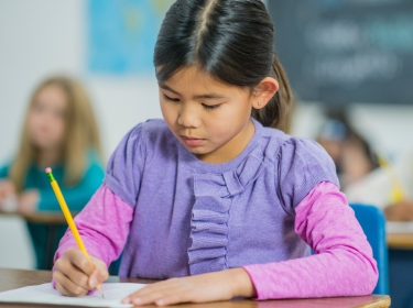 A girl is concentrating hard on a test. She is using a pencil to write, photo by FatCamera/Getty Images