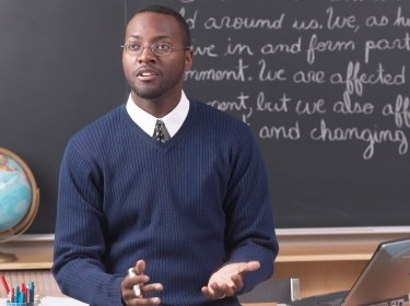 male teacher lecturing in front of chalkboard