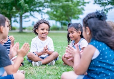 Children playing hand games in the grass