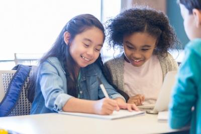 Little girls enjoy writing together at school