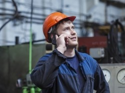 A young man in a hard hat on a worksite