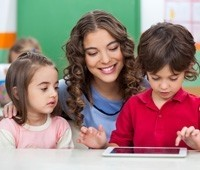 preschool students using tablet with teacher