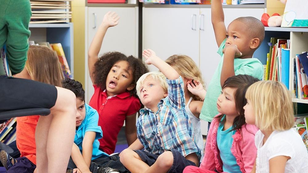 Group of preschoolers responds to their teacher