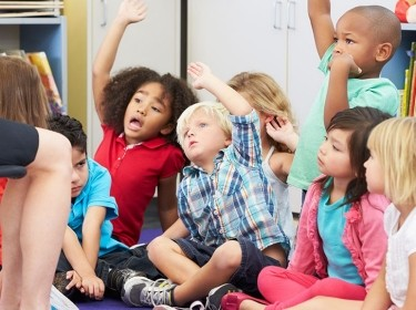 Group of preschoolers responds to their teacher