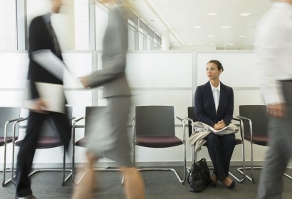 Businesswoman sitting in busy waiting area