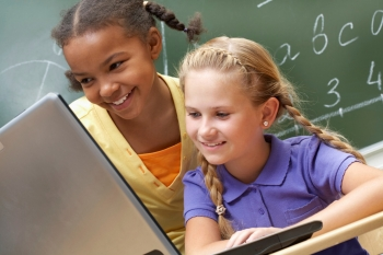 two girls in a classroom looking at a laptop computer