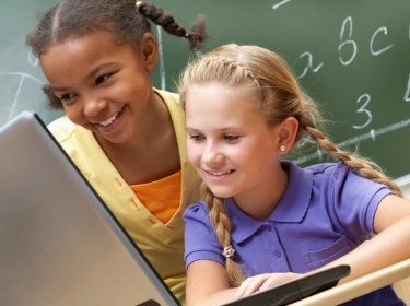 two girls looking at a laptop in a classroom