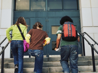 three students walking up school steps