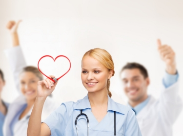 smiling doctor drawing red heart with other medical staff