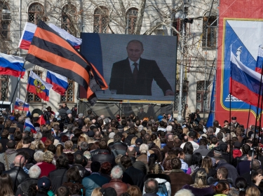 People in Sevastopol, Ukraine watch a broadcast of Russian President Putin's address to the Federal Assembly