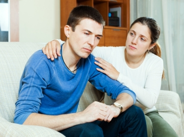 A woman consoles her husband who is depressed