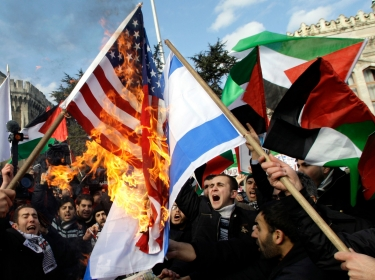 Turkish demonstrators chant Islamic slogans as they set fire to US and Israeli flags outside the Beyazit mosque in Istanbul, January 9, 2009