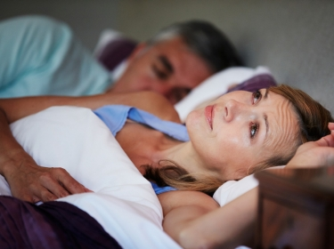 A couple in bed though the woman is suffering from insomnia