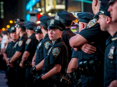 New York City Police officers watch protesters during a peaceful demonstration, as communities react to the shooting of Michael Brown in New York's Times Square August 14, 2014