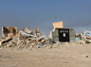 A destroyed building with a wall painted with the black flag commonly used by Islamic State militants in the town of al-Alam, Iraq, March 10, 2015