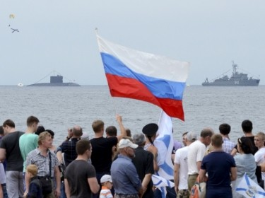 People gather to watch celebrations for Navy Day, with a Russian warship and a submarine seen in the background, in Vladivostok, Russia, July 26, 2015
