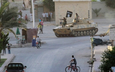 Islamist fighters having a military parade in Syria's northern Raqqa province June 30, 2014