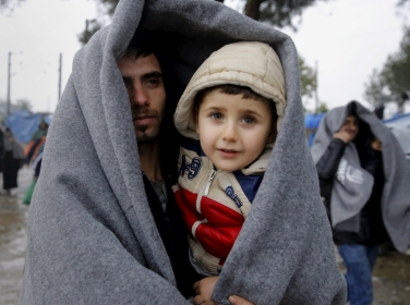 A Syrian refugee carries his son through a rainstorm at the Greek-Macedonian border near the Greek village of Idomeni, November 27, 2015
