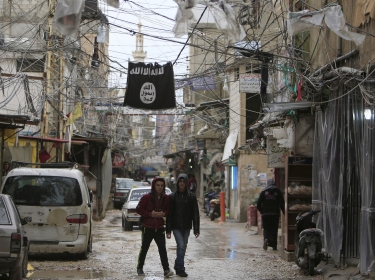 Youth walk under an Islamic State flag in Ain al-Hilweh Palestinian refugee camp, near the port-city of Sidon, Lebanon, January 19, 2016