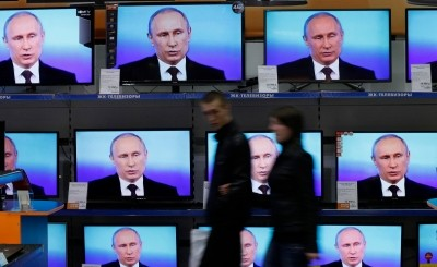 Visitors walk past TV sets during Russian President Vladimir Putin's live broadcast nationwide phone-in at the DNS electronic shop in Russia's Siberian city of Krasnoyarsk, April 17, 2014