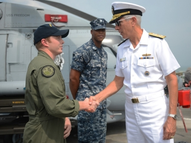Naval aircrewman aboard the littoral combat ship USS Freedom shakes hands with Adm. Samuel J. Locklear III, commander of U.S. Pacific Command, Singapore, June 3, 2013