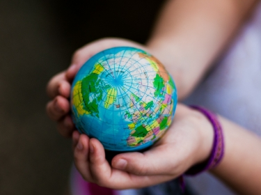 A child's hands holding a small globe