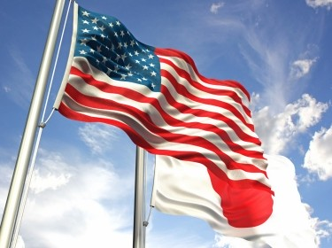 American and Japanese flags waving against the sky