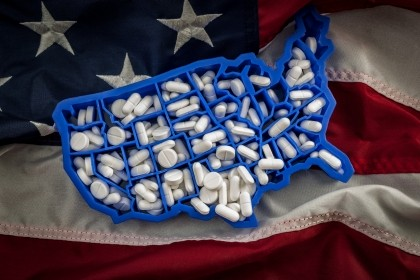 Healthcare, opioid epidemic and drug abuse concept with the map of USA filled with oxycodone and hydrocodone pharmaceutical pills on the American flag, photo by Victor Moussa/AdobeStock