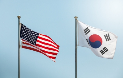 The American flag and the South Korean flag on blue sky, photo by ByoungJoo/Getty Images
