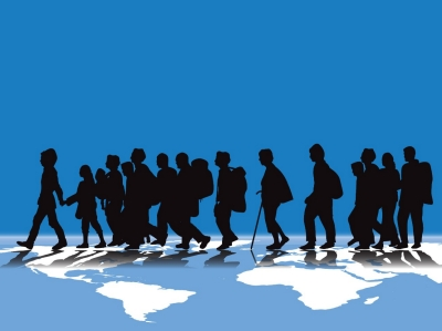 An illustration of migration using silhouettes of people walking across the globe. Image by Carlos Gardel / Adobe Stock