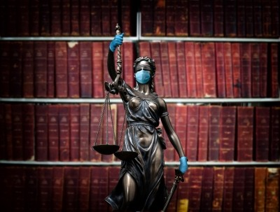 A statue of Themis wearing a face mask and gloves, in front of volumes of law books. Photo by 101cats / Getty Images