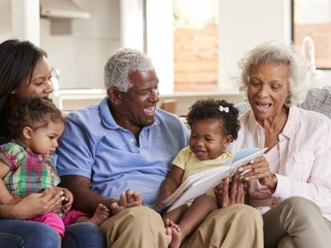 Multi-generation family sitting on sofa at home reading book with baby granddaughters, photo by Monkey Business/AdobeStock
