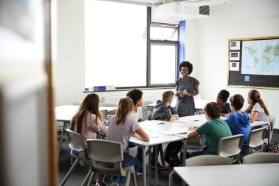Female high school teacher standing by table with students teaching lesson, photo by Adobe Stock