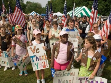 Girl Scouts from across eastern Massachusetts welcome home more than 50 base Airmen June 27 at Hanscom Air Force Base, Mass. The gathering was part of a Heroes' Homecoming celebration. Earlier this year, hundreds of Girl Scouts came to Hanscom AFB to deliver more than 10,000 boxes of Girl Scout cookies that were sent to deployed military members around the world, photo by Rick Berry/U.S. Air Force