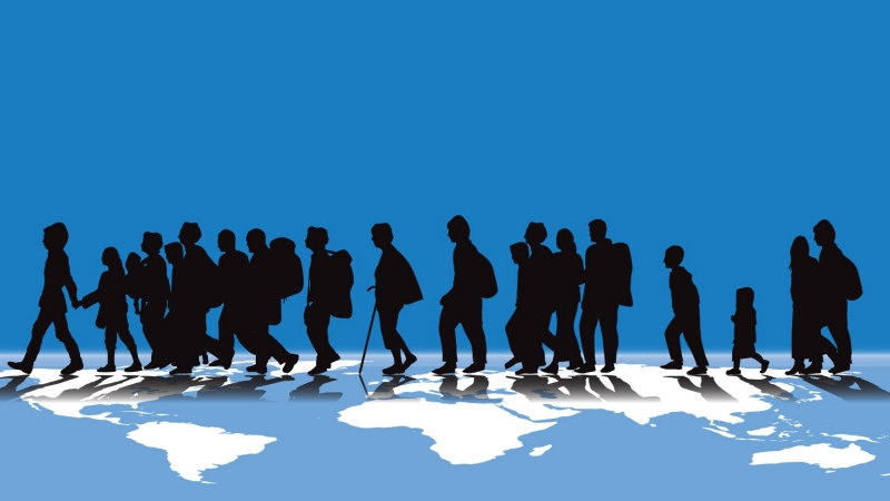 Silhouettes of migrants walking across a world map.